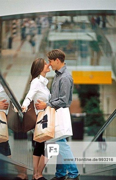 Paar mit Einkaufstaschen auf Scalator in Shopping-mall