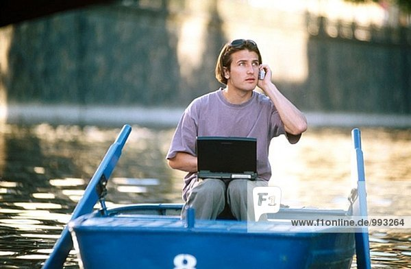 Man on rowboat using cellular phone and laptop