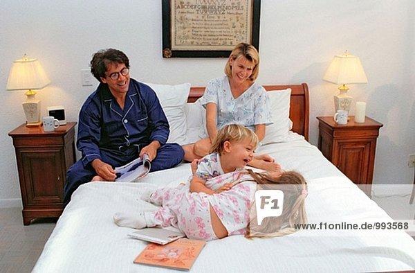 spielerische Familie auf einem Bett
