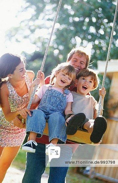 spielerische Familie-Kinder auf eine Schaukel
