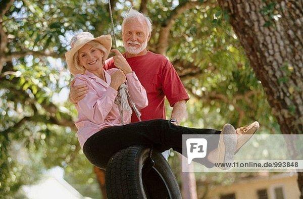 älteres Paar auf einem Reifen-swing