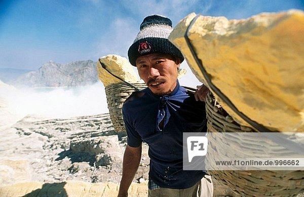 Miner mit hoher Auslastung der gelben elementarem Schwefel zusammengestellt von innerhalb der aktiven Krater der Vulkan Ijen  Ost-Java  Indonesien