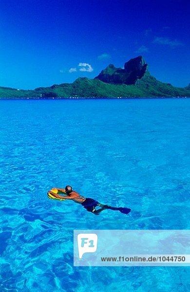 Lagune mit Schwimmer in Lagune im Vordergrund. Bora Bora. Leeward-Inseln. Französisch-Polynesien