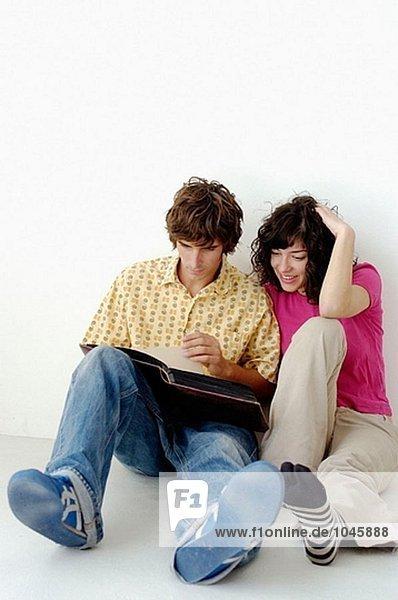 Paar sitzen auf dem Boden gerade ein Buch
