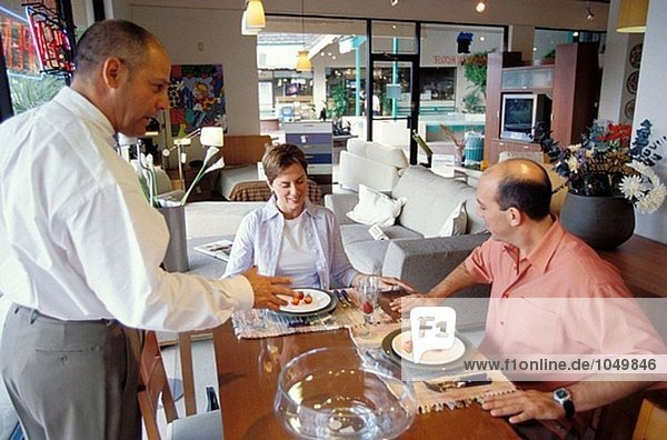 Couple and salesman in furniture shop