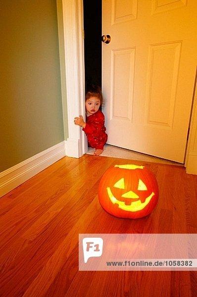 Halloween Jack-O´-Laterne mit Angst kleinen Mädchen um Ecke spähen