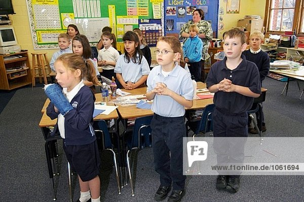 First grade students saying prayers in class. Catholic school