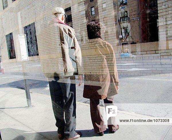 Reflektierte Blick auf ein älteres Ehepaar warten auf einen Bus in New York City. USA