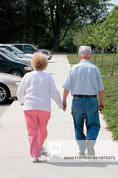 Seniror paar gehen Hand in Hand hinunter ein Bürgersteig