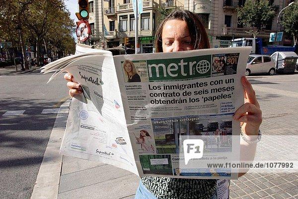 Woman reading Metro free newspaper in Barcelona. Spain