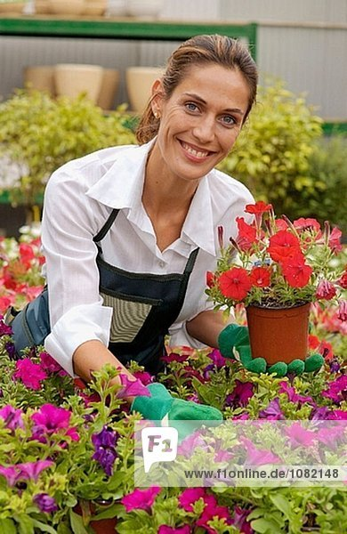 Frau hält Topf mit Surfinias an Gartencenter