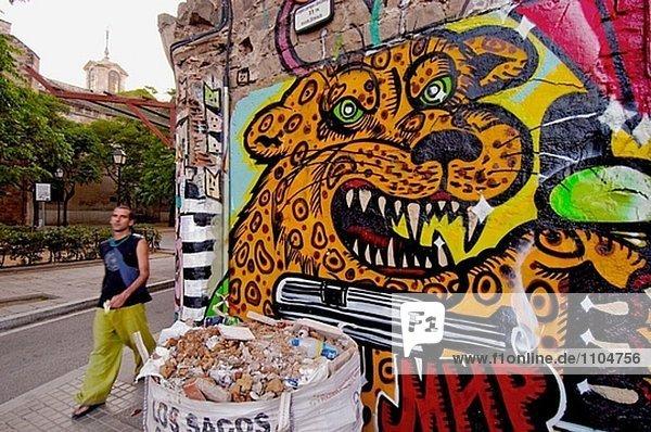 Graffiti-Wand mit Passanten im Stadtteil El Raval. Barcelona. Spanien