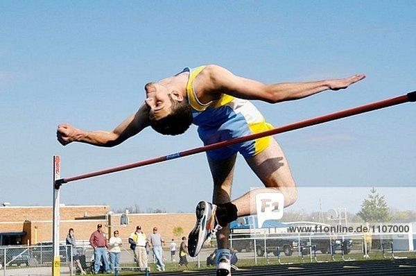 Hochspringer löscht die Bar in einem High-School-Track-Wettbewerb