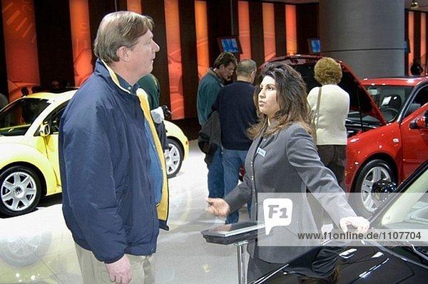Sales Frau spricht mit Käufer über Features auf Auto.