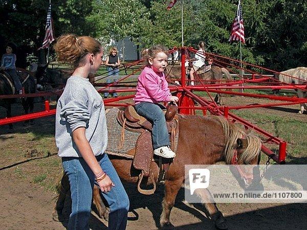 Mutter Beihilfen Tochter in ein live Pony Reiten
