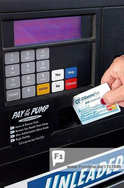 Frau zahlt an der Zapfsäule mit eine Debit-Karte.