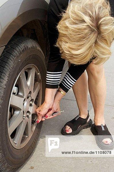 Frau Automobil Reifendruck für Luft bei Gage überprüft dann fügt air