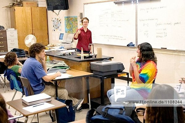 Handicapped Deaf student uses sign language to communitate in a classroom