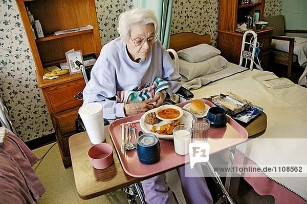 A senior female receives assistance by being served food and meals in a nursing home rehabilitation center
