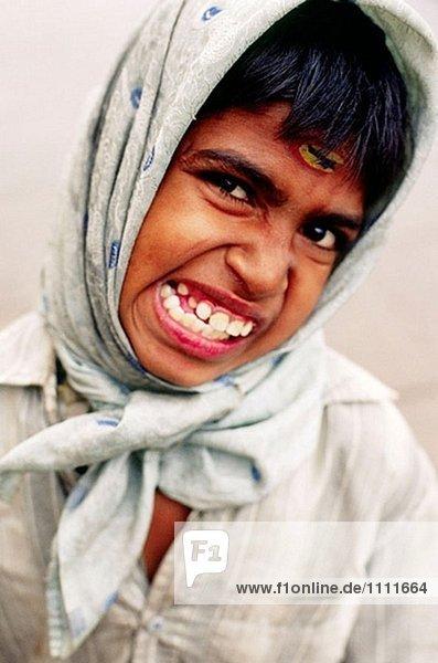 Indische junge in einem Kopftuch Schleifen seine Zähne und ziehen ein Gesicht. Varanasi  Indien c.SIKKIM