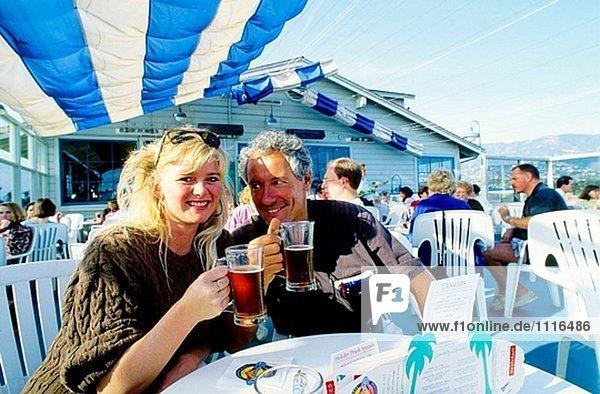 Couple on the pier having a drink. The seaside in Santa Barbara. California. USA.