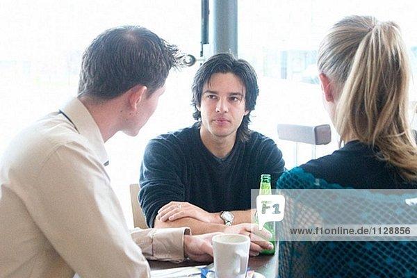 2 Mann und ein Mädchen reden bei einem Drink in einem Café