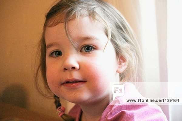 Headshot of 3 year old girl  looking looking into camera  smiling