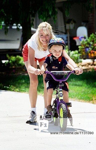 Mutter mit Sohn auf seine erste Fahrrad
