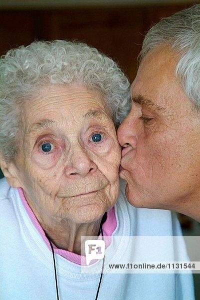 60 Jahre alten senior männlich Küsse Mutter auf die Wange an ihrem 85 Geburtstag