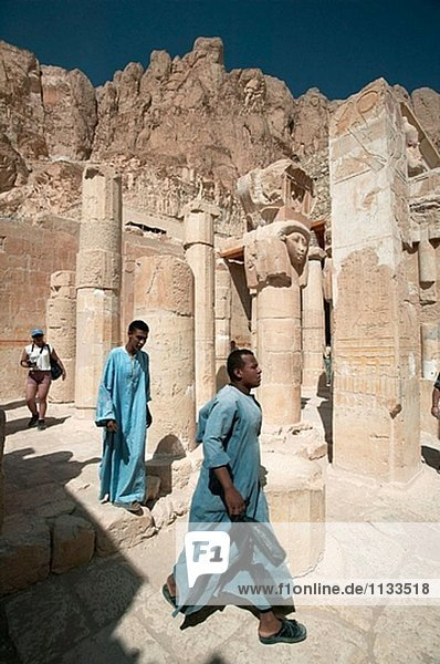 Temple caretakers walk through the broken columns at the Mortuary Temple of Hatshepsut (Deir el-Bahri).