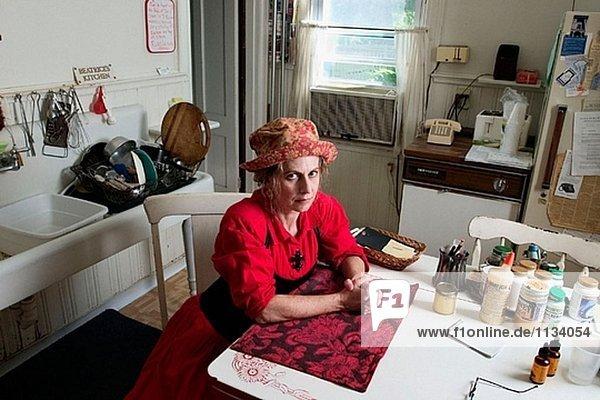Frau mittleren Alters  tragen einen roten Kleid und Hut  am Tisch in ihrer Küche  denken.