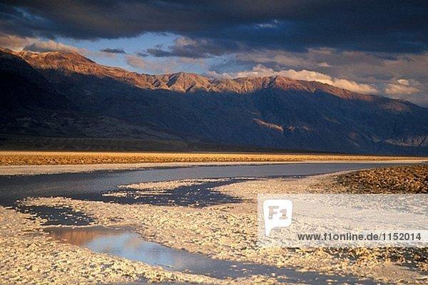 Gewitterwolken bei Sonnenuntergang auf schwarzen Berge und überflutet Salzpfanne  Devils Golf Course  Death Valley  Kalifornien