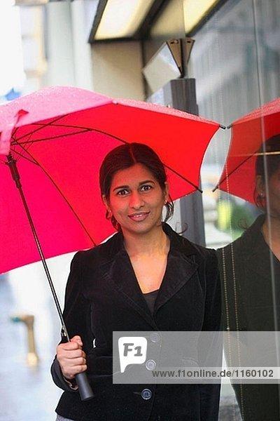 Indische geschäftsfrau mit Regen Regenschirm
