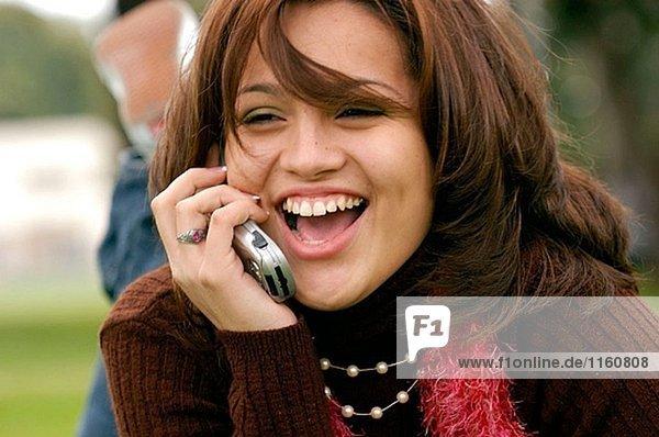 lachend Hispanic Lady auf Telefon