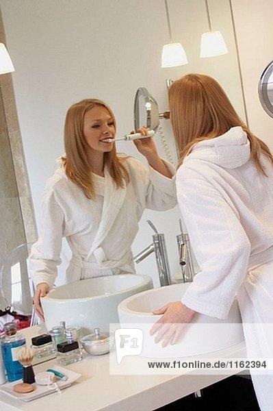 Mädchen putzen ihre Zähne in der Badezimmerspiegel Gewand