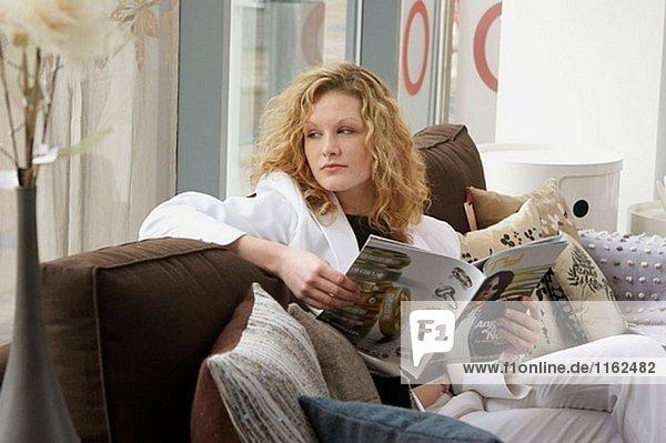 20 Jahre altes Mädchen sitzen auf dem Sofa mit einem Buch  Wegsehen