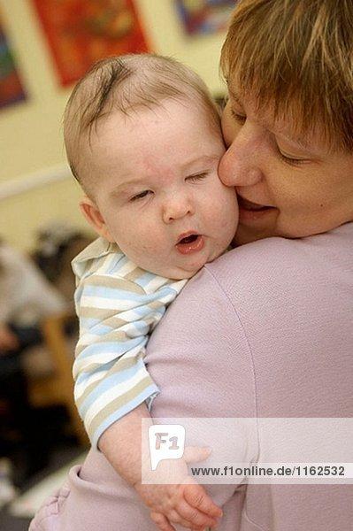 Baby liegen auf ihre Mütter Schulter Gähnen.