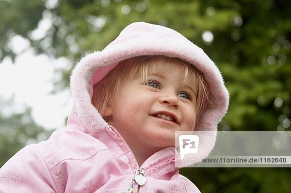 18 month old girl outside  with her hood up  smiling