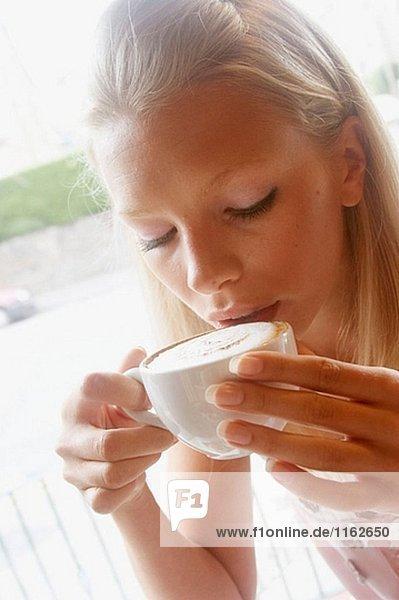 21 Jahre altes Mädchen sitzt in einem Café Kaffee zu trinken