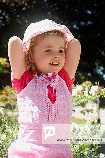 3-jähriges Mädchen sitzen an einer Wand außerhalb  mit den Händen hinter dem Kopf lächelnd