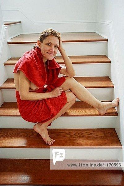 40´s hellhäutige Frau umwickelt Handtücher nude sitzen auf Schritte Lächeln in die Kamera