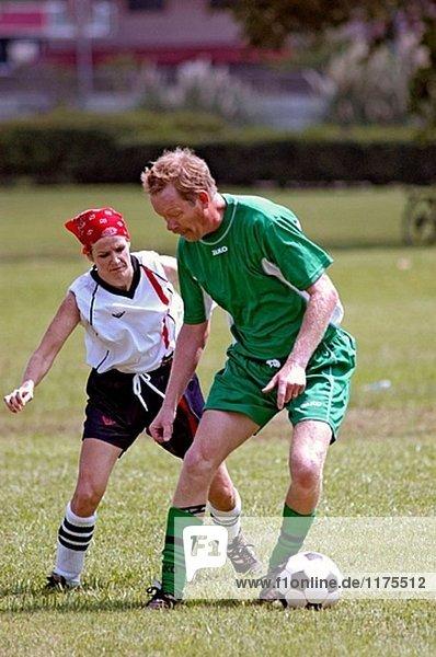 Man Fußball spielen gegen eine Frau auf Feld während eines Spiels