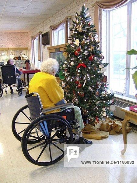 Senior Frau sitzt in einem Rollstuhl neben einem Weihnachtsbaum während der Sanierung von einem Sturz in einem Pflegeheim