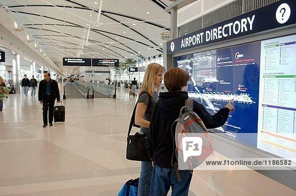 Frau und junge überprüfen Sie Flughafen Directory in Detroit Flughafen. Michigan  USA