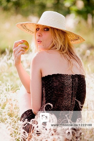 Young blonde woman with apple sitting in green grass