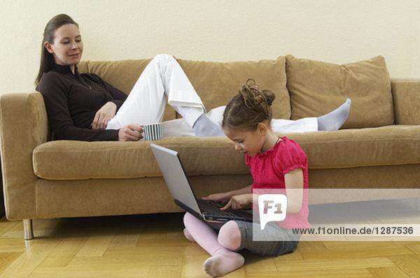 Mutter liegend auf Sofa beobachten ihrer kleinen Tochter auf Computer eingeben