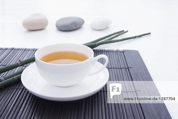Stillleben mit Teetasse auf Stroh Matte mit drei Kieselsteinen im Hintergrund