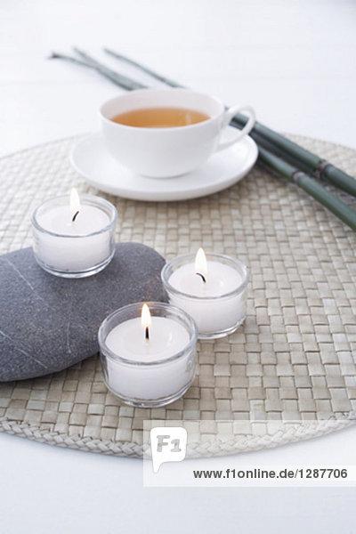 Stillleben mit drei Kerzen mit Teetasse im Hintergrund