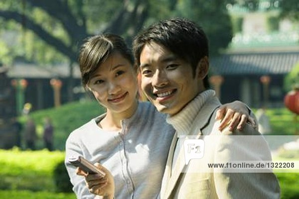 Young couple with cell phone  smiling at camera  portrait