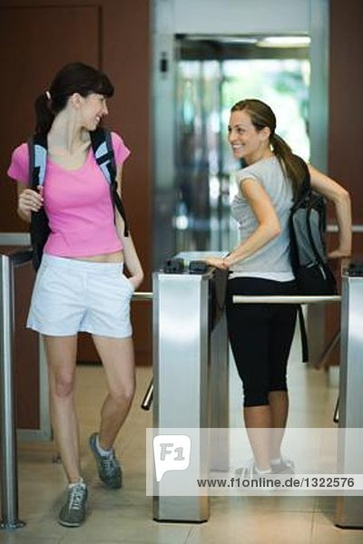 Two women going through turnstile at health club  looking over shoulders at each other